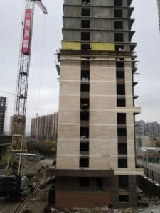 Строительный кран рядом со строящийся многоэтажкой